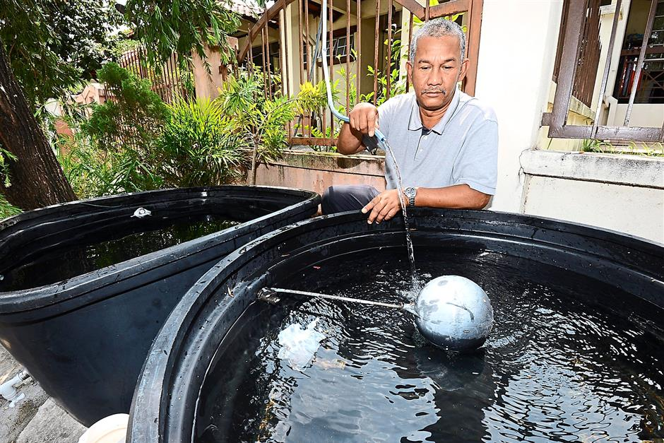 Abdul Rahman Mohamad, a guard in Taman Damai Murni Cheras, refilling a water tub on behalf of Mohd Rizal, who provided water to his neighbours.