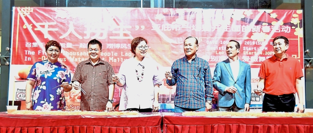 Liew (third from left) and Tan (fourth from left) leading the mass yee sang tossing ceremony at Oceanus Mall.