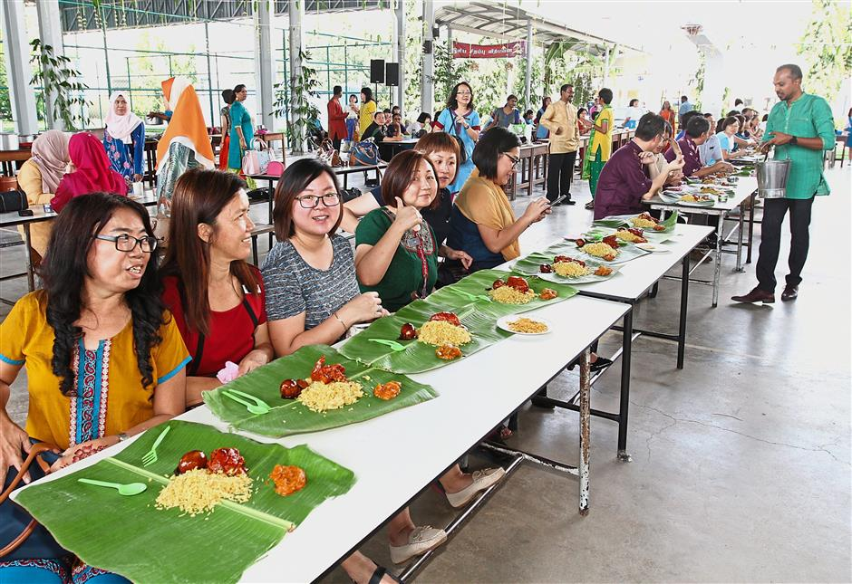 (Top) Teachers and guests enjoying briyani served on banana leaf after the celebration. (Left) A dancer performing an Indian classical dance during the celebration.