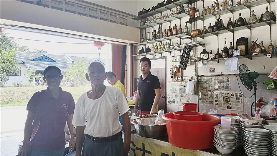 Chin (left) with three generations in the Loh family, Chin Seng (second from left), Pak Choy (yellow shirt) and Jing Xian (black shirt) at their shop in Kampung Baru Paya.