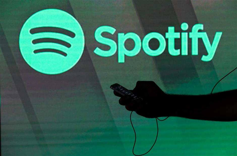 A man checks his smartphone whilst standing amongst illuminated screens bearing the Spotify Technology SA logo in this arranged photograph in London, U.K., on Tuesday, June 26, 2018. Spotify Technology SAu00a0hired Dawn Ostroff as its chief content officer, tapping a Conde Nast entertainment executive to oversee music, audio and video partnerships. Photographer: Chris Ratcliffe/Bloomberg