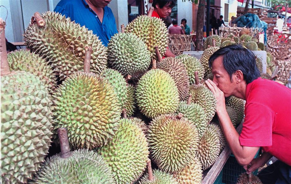 Most nutritious: A buyer sniffing for a good choice. Research has already been conducted from China to Singapore and yielded many positive benefits by indulging in the 'king of fruits'. — Reuters