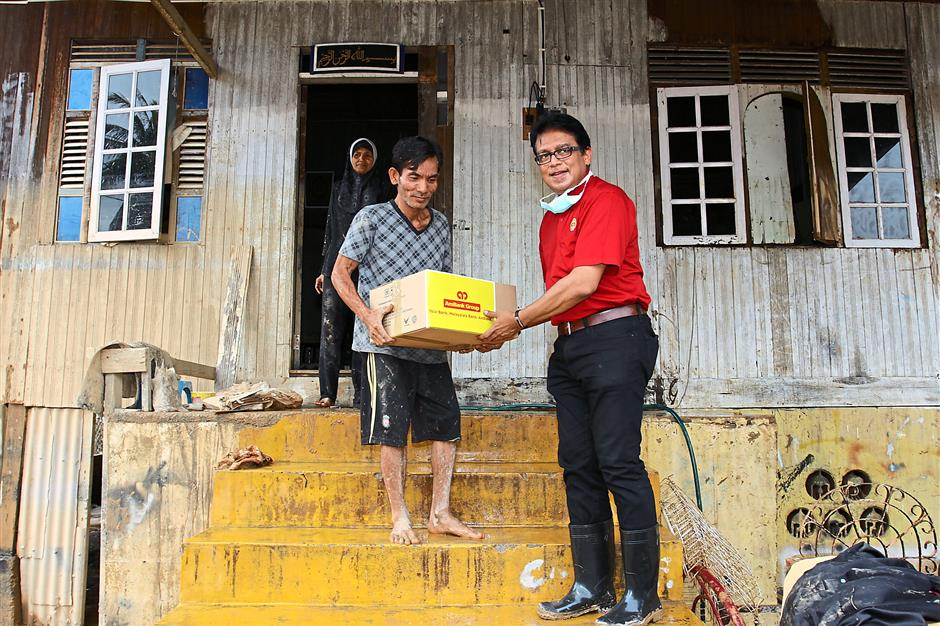 Necessities: Syed Anuar handing over essential items to a resident in Kampung Sireh, Kota Bharu.
