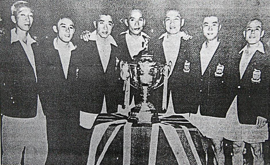 Malayan team with the Thomas Cup after beating Denmark 8-1 in the 1955 final in Singapore. Tan Jin Eong is on the right.