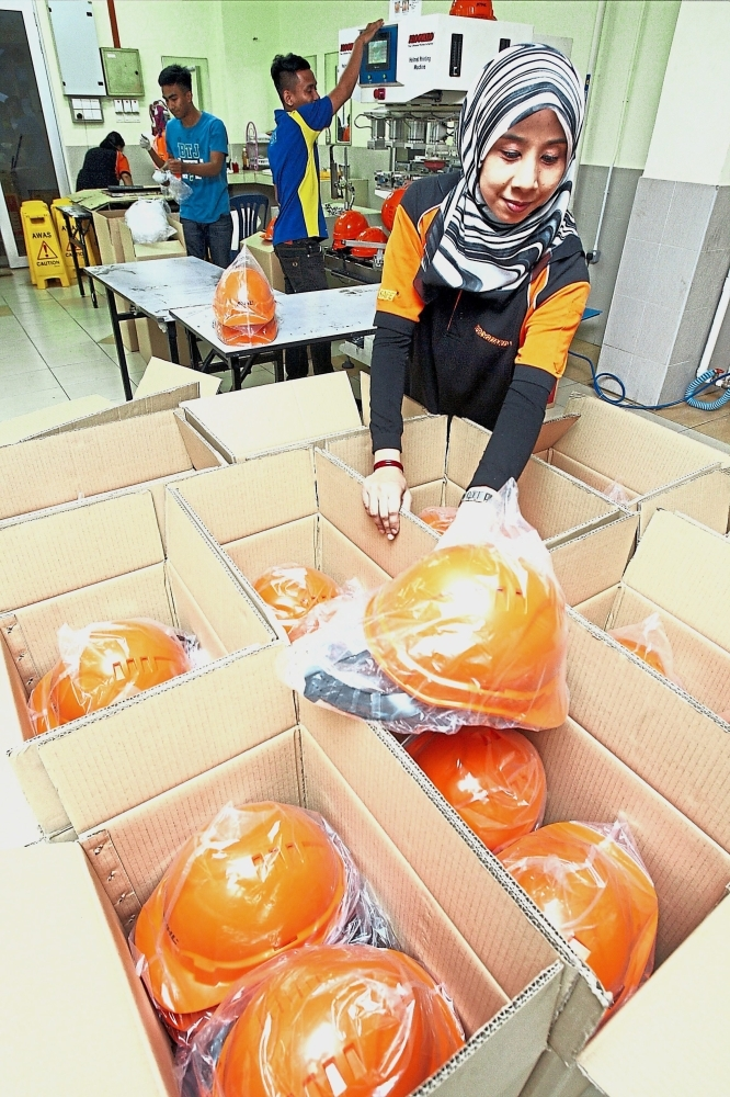 Workers packing the safety helmets at the facility. — Photos: S.S.KANESAN/The Star