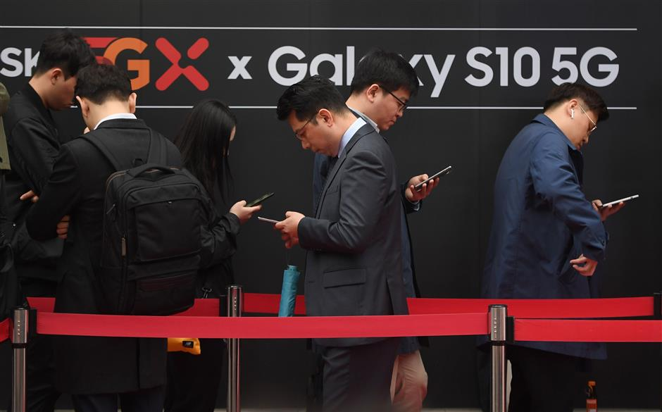 People wait in line to buy new Samsung Galaxy S10 5G smartphones in front of an SK Telecom shop during a launch event in Seoul on April 5, 2019. - The world's biggest smartphone and memory chip maker Samsung Electronics warned of a 60 percent-plus plunge in first-quarter operating profits on April 5, in the face of a weakening chip market. Samsung was also launching its top-end Galaxy S10 5G smartphone, after South Korea this week won the global race to commercially launch the world's first nationwide 5G networks. (Photo by JUNG Yeon-Je / AFP)