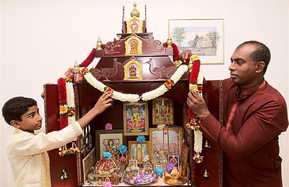 Time with family: Kunasekaran (right) and his eldest son Manish decorating the altar at their home with garlands for the celebration.