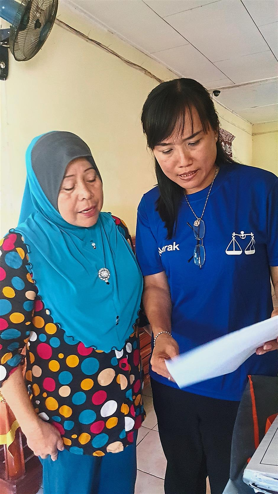 Hajijah (left) showing Liew the documents for her medical appointment at the Raja Permaisuri Tuanku Bainun Hospital in Ipoh. – FOONG PEK YEE/The Star