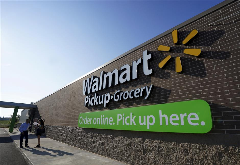 FILE PHOTO: People talk outside a Wal-Mart Pickup-Grocery test store in Bentonville, Arkansas, June 4, 2015.  Customers using the store place their orders online and then pick up their merchandise in a drive-through. REUTERS/Rick Wilking/File Photo