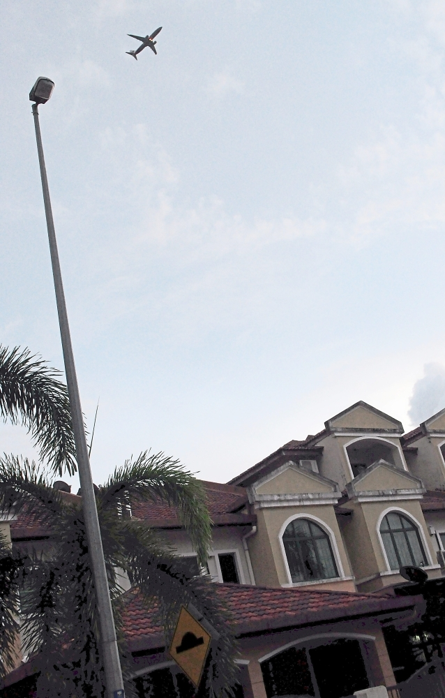 An aircraft flying over a row of houses in Kota Warisan. Residents say they have to put up with the noise even in wee hours of the night.