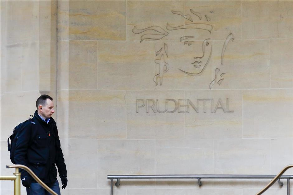 A pedestrian passes a Prudential Plc logo on the wall of the building housing their headquarters in London, U.K., on Thursday, March 15, 2018. Prudential soared on plans to split the firm by spinning off its U.K. operations, a move that will create an insurance business focused on faster-growth markets in Asia, Africa and the U.S. Photographer: Luke MacGregor/Bloomberg
