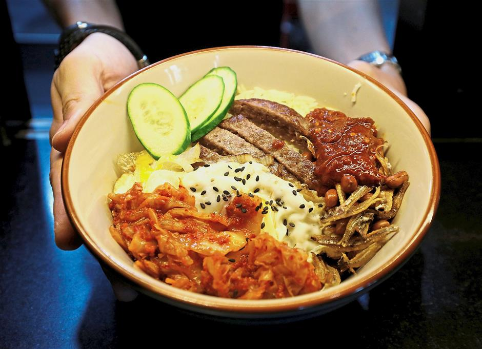 Delicious twist: A bowl of Trump-Kim nasi lemak, made from dry-aged US beef and kimchi, at Harmony Nasi Lemak restaurant. — Reuters