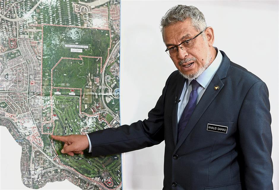 Khalid showing the area of the proposed development at Taman Rimba Kiara during the interview.