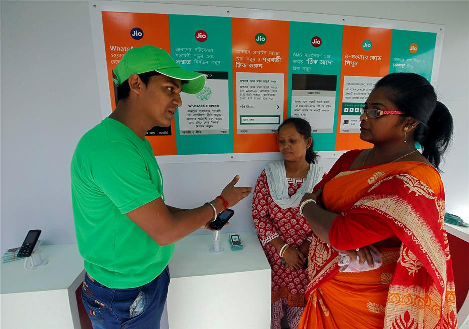 A WhatsApp-Reliance Jio representative explains how to use Facebook Inc's WhatsApp messenger to a woman during a drive by the two companies to educate users, on the outskirts of Kolkata, India, October 9, 2018. Picture taken October 9, 2018. REUTERS/Rupak De Chowdhuri