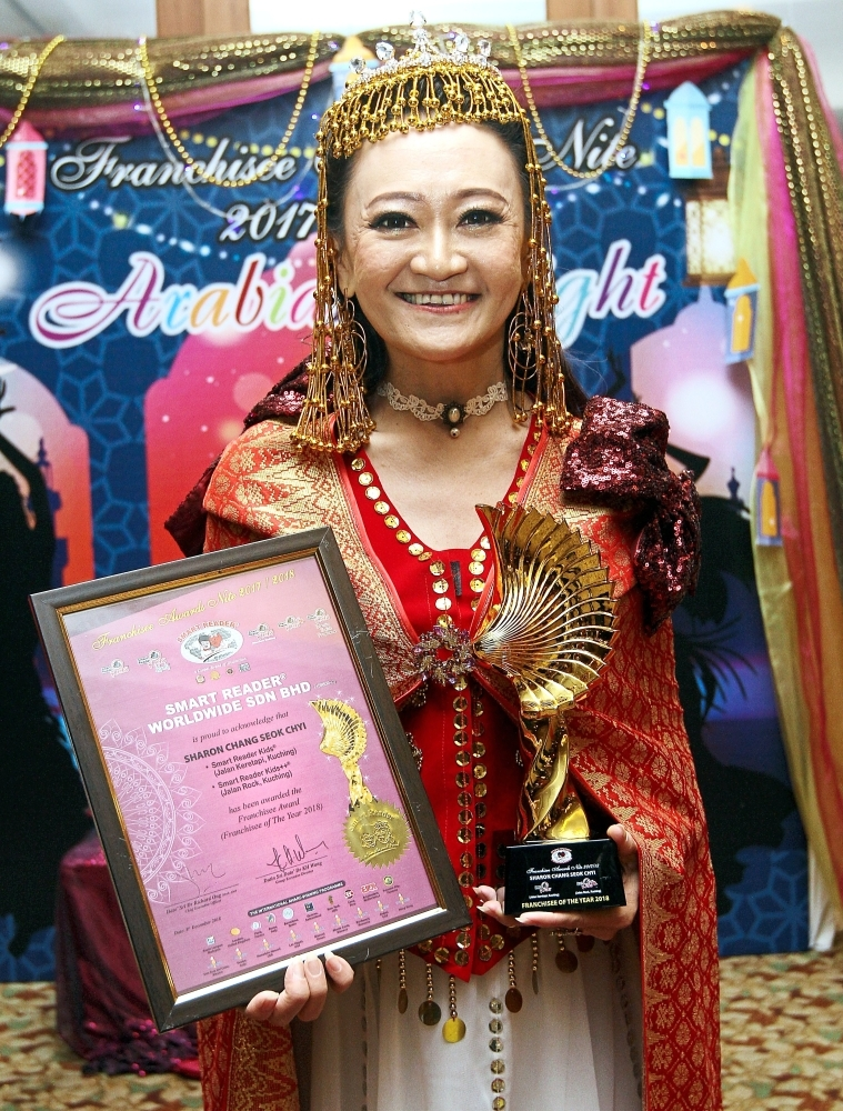Chang holding her Franchisee of the Year Award while donning a creative Arabian-inspired costume.