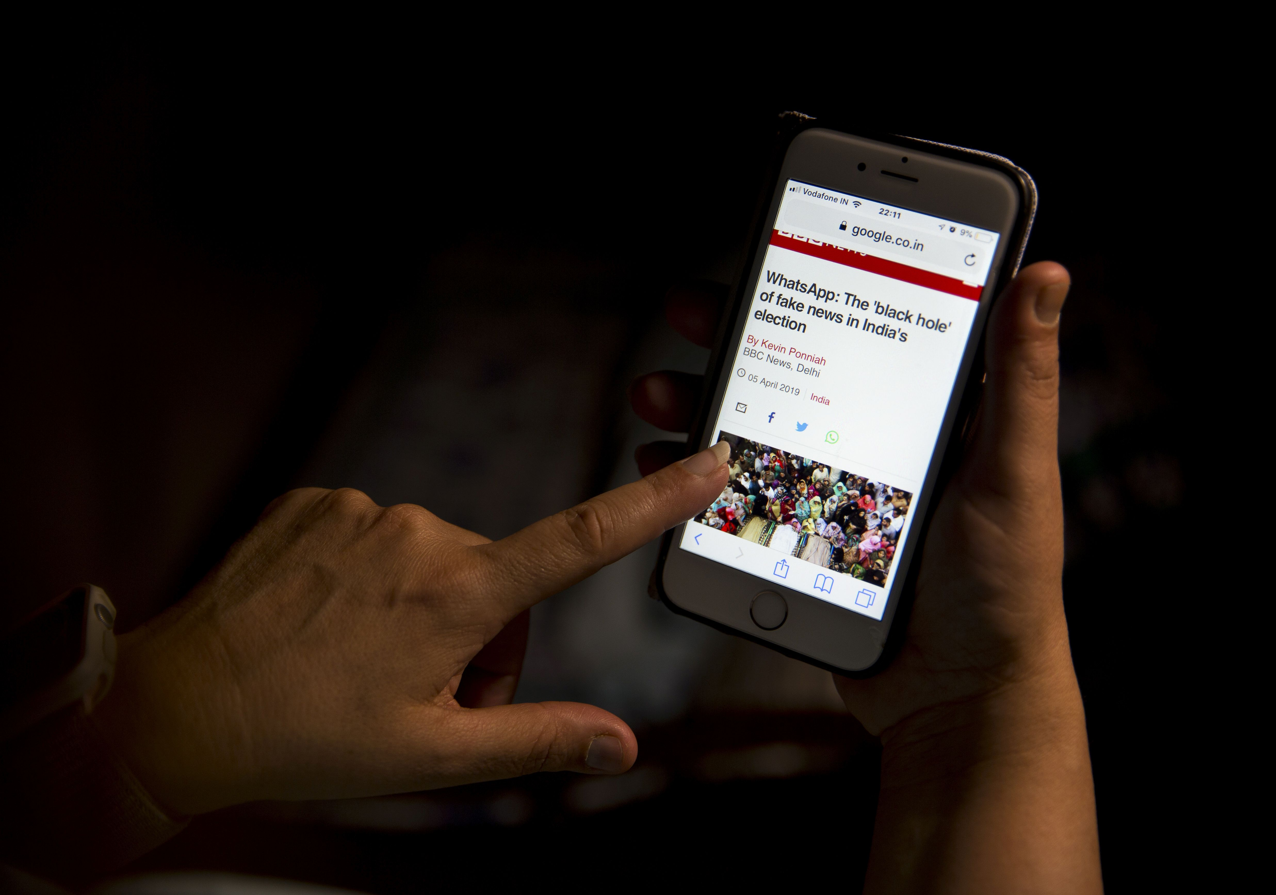 In this Monday, April 8, 2019, photo, a woman reads an article on her mobile phone concerning the chances of fake news in India during the upcoming elections in New Delhi, India. From manipulated pictures being picked up by mainstream news media, to misrepresented quotes sparking communal division, false news and hateful propaganda on digital platforms are at peak levels in the run-up to the Indian general elections (AP Photo/Manish Swarup)