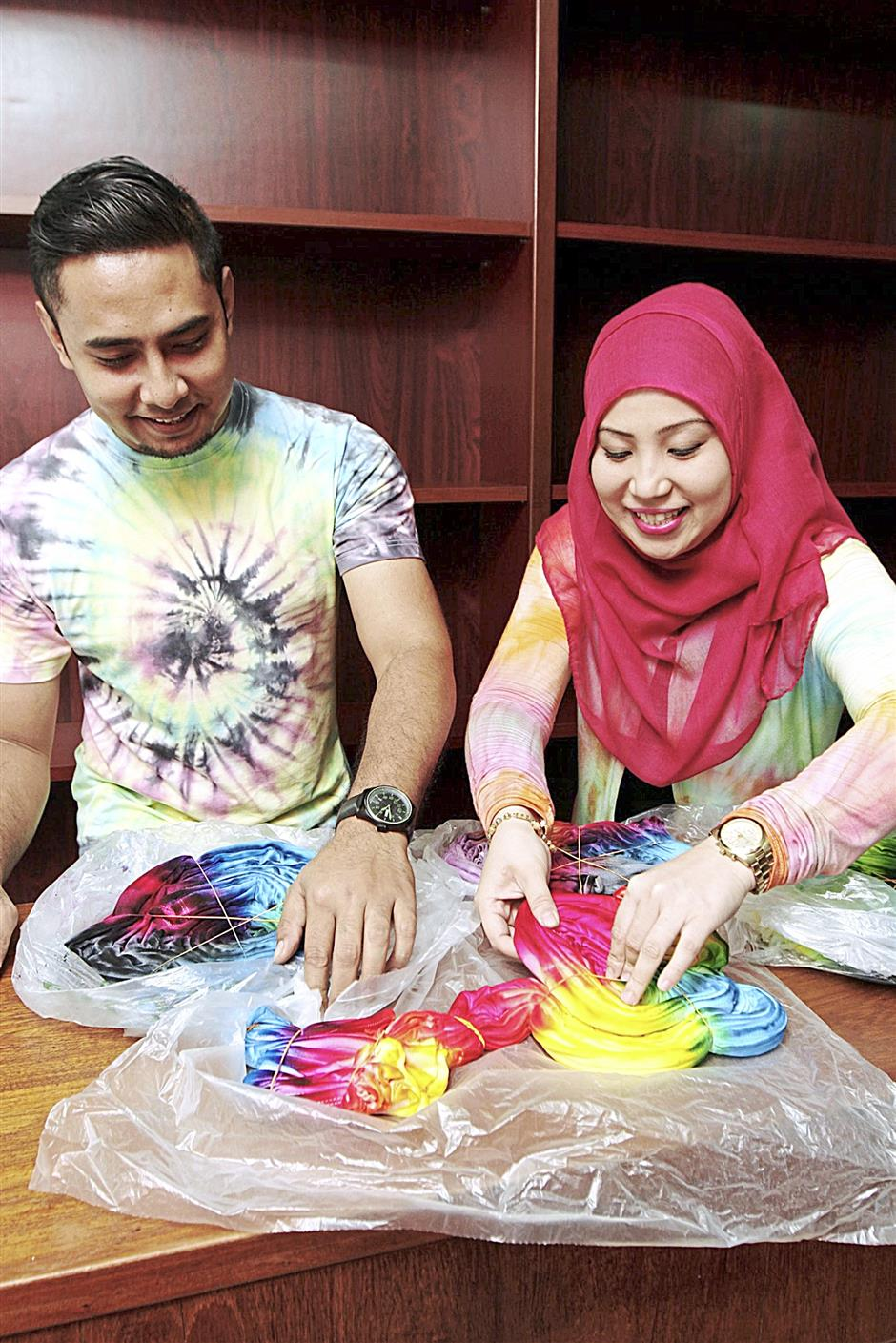 Abdul Hafiz and Khairunnisa demonstrating how the tie-dye process is done.