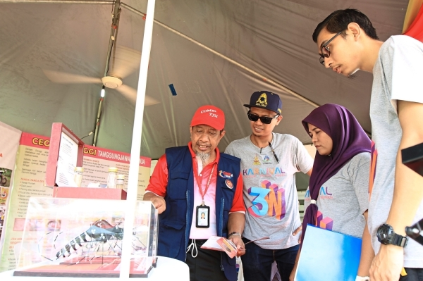 Mohd Salleh (in red cap) explaining the dangers of dengue and Aedes mosquitoes to visitors.