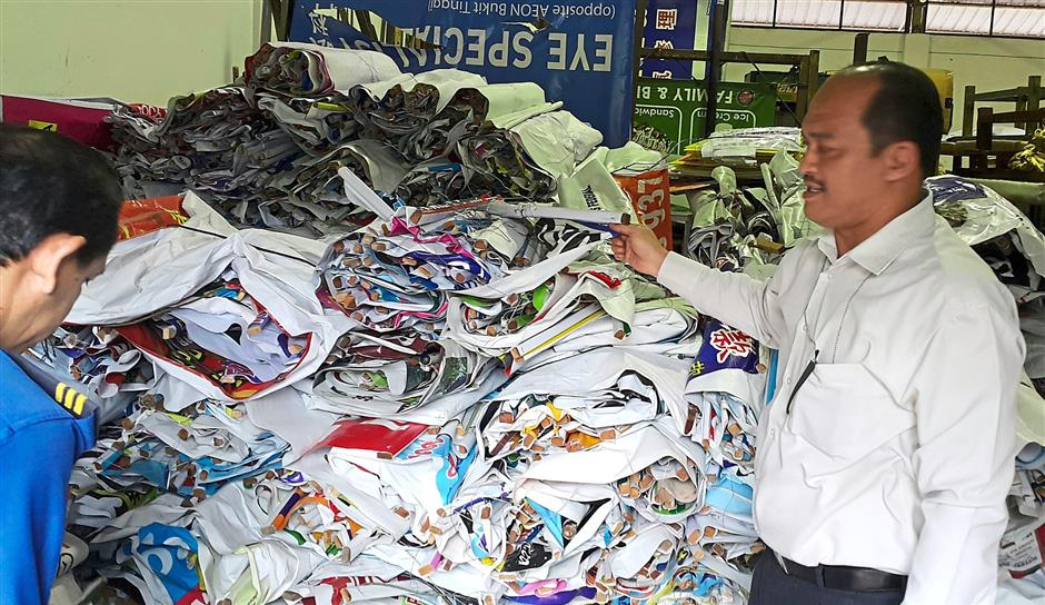 Klang Municipal Council enforcement chief Andry Arman showing the council's store that is filled with illegal banners and posters that have been taken down.