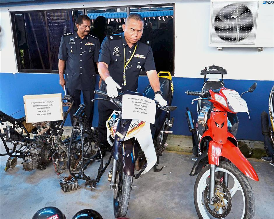 Penampang District Police Chief DSP Rosley Hobden (right) and his officer showing the seized stolen motorcycle frames and parts during press conference at Penampang police station. (Nov09)(picture goes with story slug kkmthieves091117)