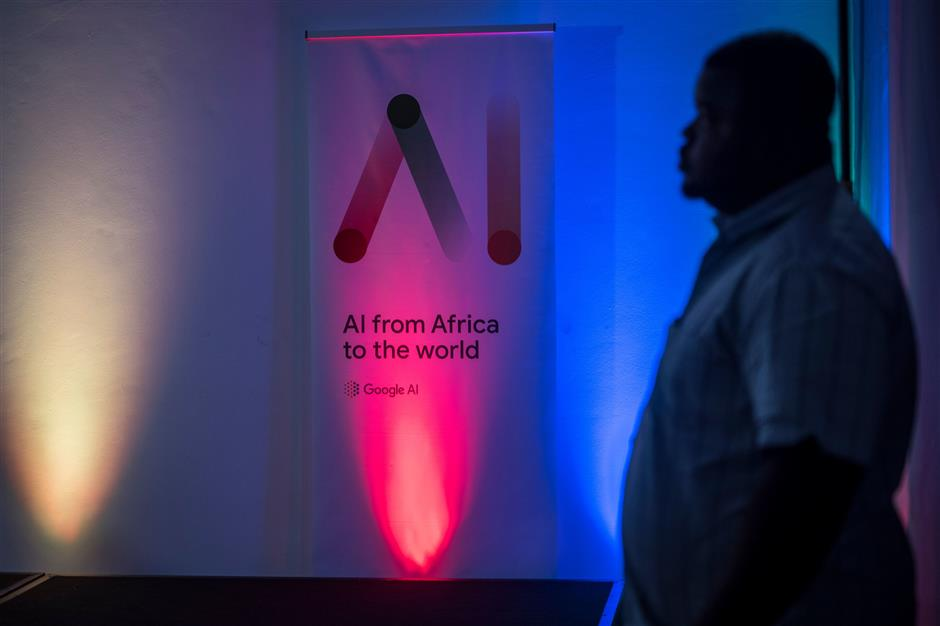 A journalist stands next to a Google Artificial Intelligence (AI) poster during the presentation of the first AI centre in Africa at Marriott hotel in Accra on April 10, 2019. - This centre is the first AI centre established in Africa by Google. (Photo by CRISTINA ALDEHUELA / AFP)