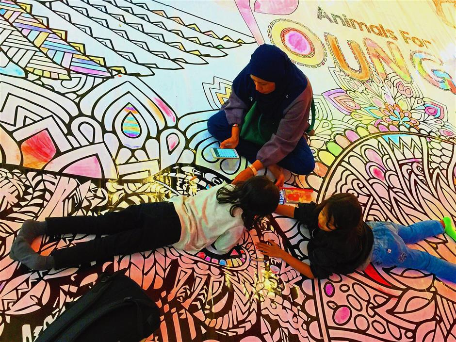 (Left) Children getting a little help in colouring the giant poster.
