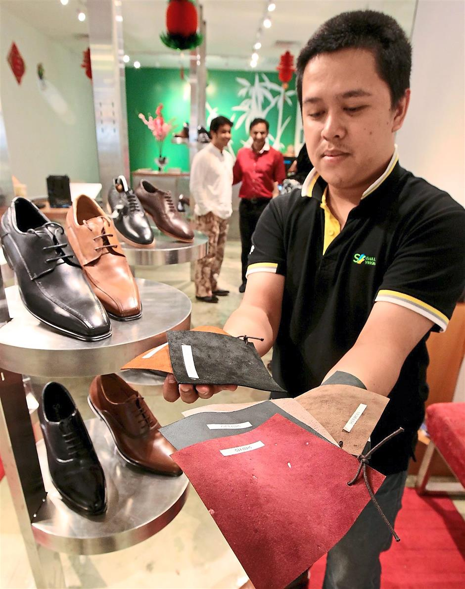 Material comfort: A Solace sales assistant showing off the different types of calf and cow leather used in making the shoes.
