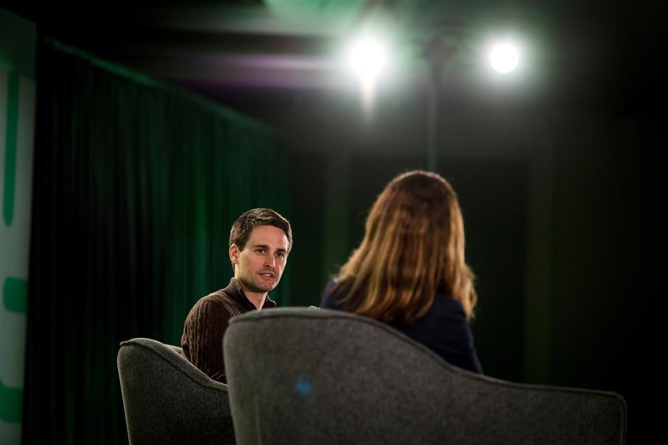 Evan Spiegel, co-founder and chief executive officer of Snap Inc., left, speaks during the New Work Summit in Half Moon Bay, California, U.S., on Monday, Feb. 25, 2019. The event gathers powerful leaders to assess the opportunities and risks that are now emerging as artificial intelligence accelerates its transformation across industries. Photographer: David Paul Morris/Bloomberg