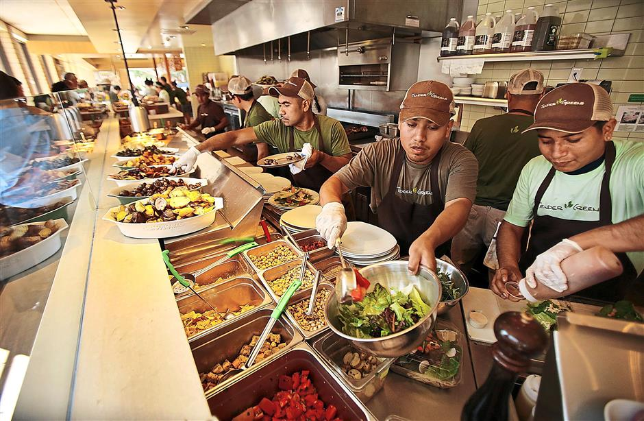 (From left) Pedro Gomez, Martin Garcia and Jaime Lopez, salad makers working the line, prepare lunch for customers at Tender Greens, Santa Monica, California in the United States.