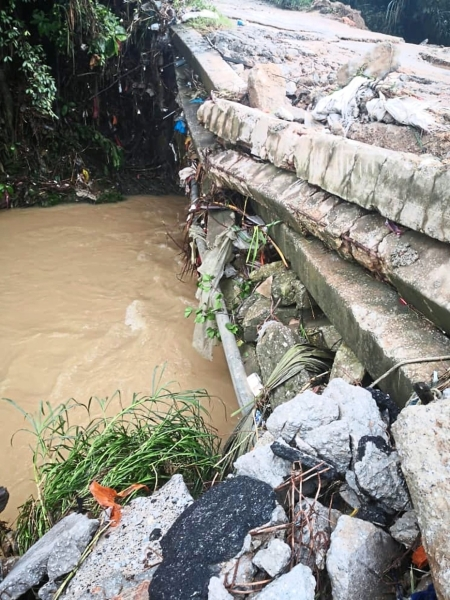 A stream that leads to Sungai Gong is blocked by concrete from a damaged bridge.