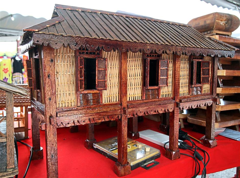 A miniature wooden Rumah Kutai.