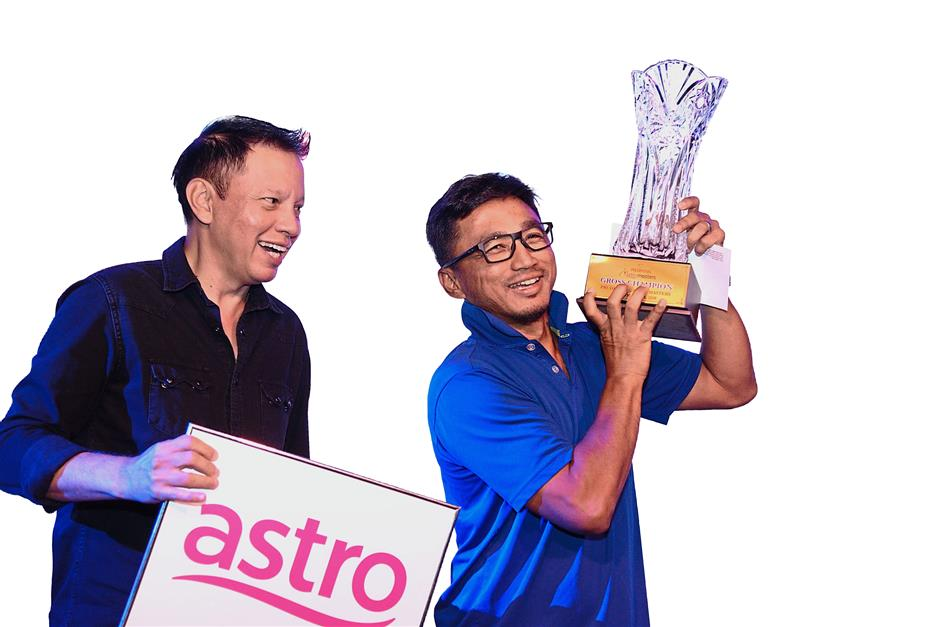 Jubilant Mohd Hezri lifts the champion's trophy watched on by Astro's Datuk David Yap.