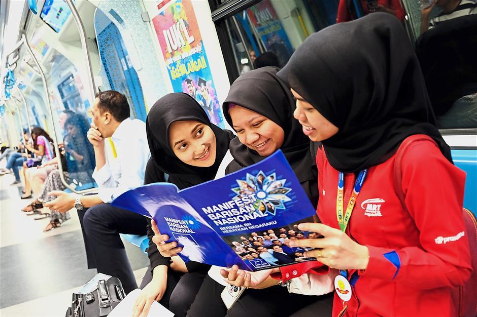 Nabilah Ruslan, 27, Ainul Marziah Nazir, 24, and Norelmi Amalina Abu Hassan, 25, looking through a copy of the Barisan Nasional manifesto. – Bernama