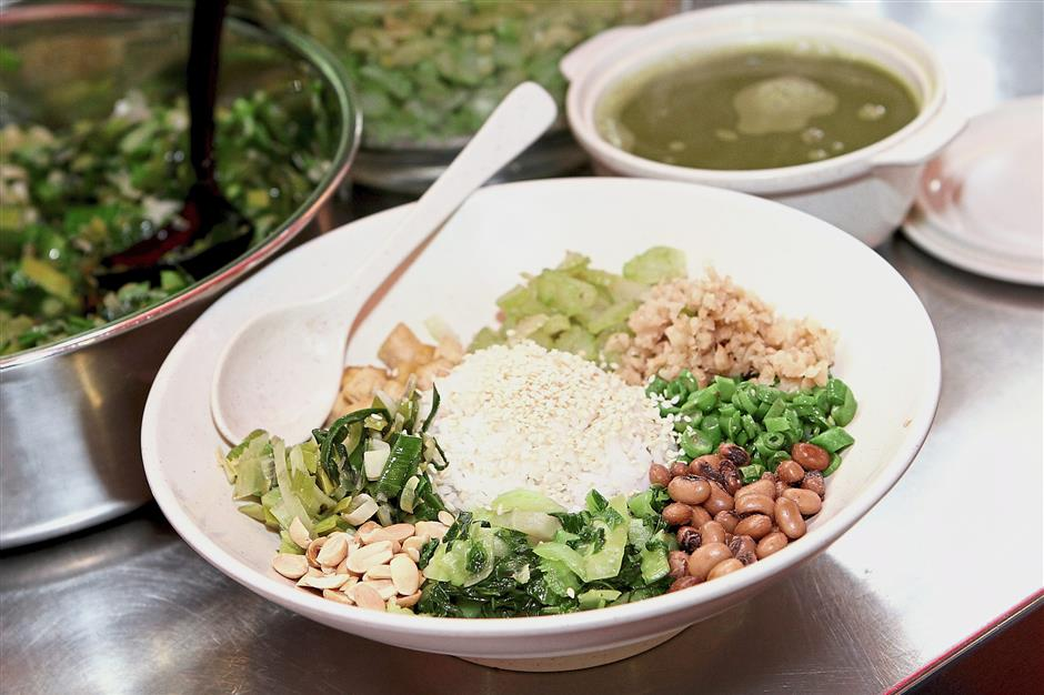 The bowl of Hakka lei cha rice loaded with different greens and peanuts, topped with white sesame.