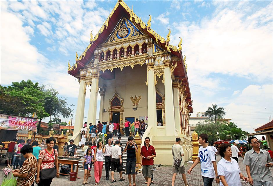 Devotees praying and offering flowers to Buddha outside the Thai Buddhist Chetawan Temples shrine hall during Wesak day.