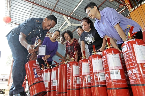 Dr Ang (right) and residents of Lim Jetty learning how to operate a fire extinguisher during a briefing at the Community-based Fire Preparedness and Response Strategy programme at Lim Jetty in Weld Quay, George Town.