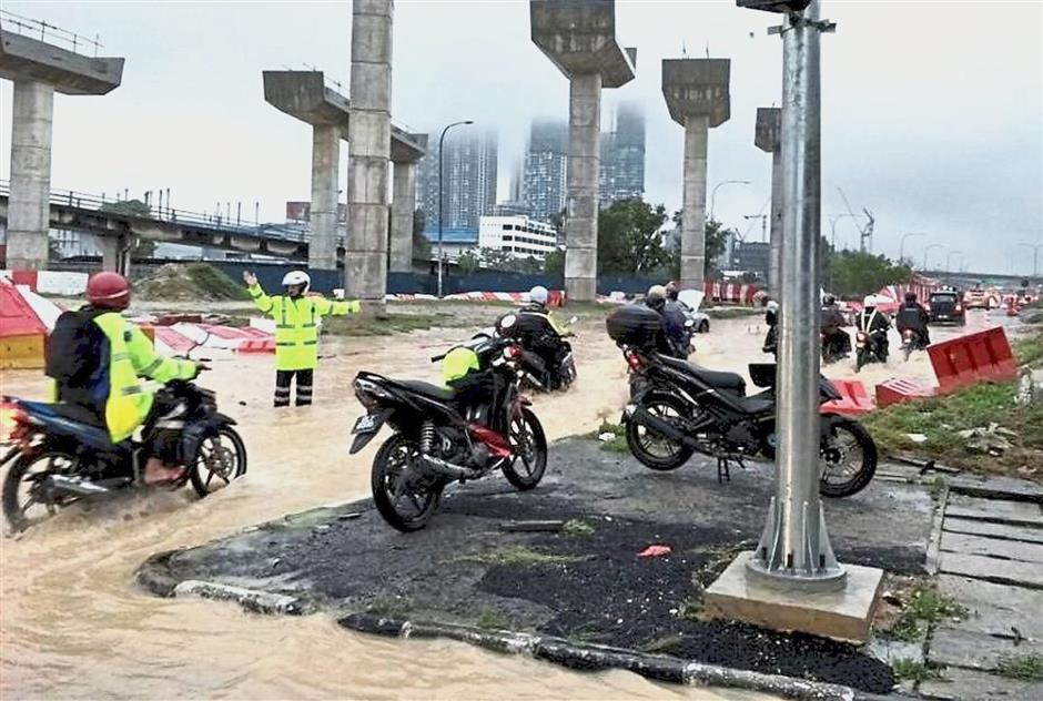(Left) Traffic police personnel were deployed to manage traffic flow as well as to close some roads.(Below) Motorists inching their way through the flood waters in Klang.