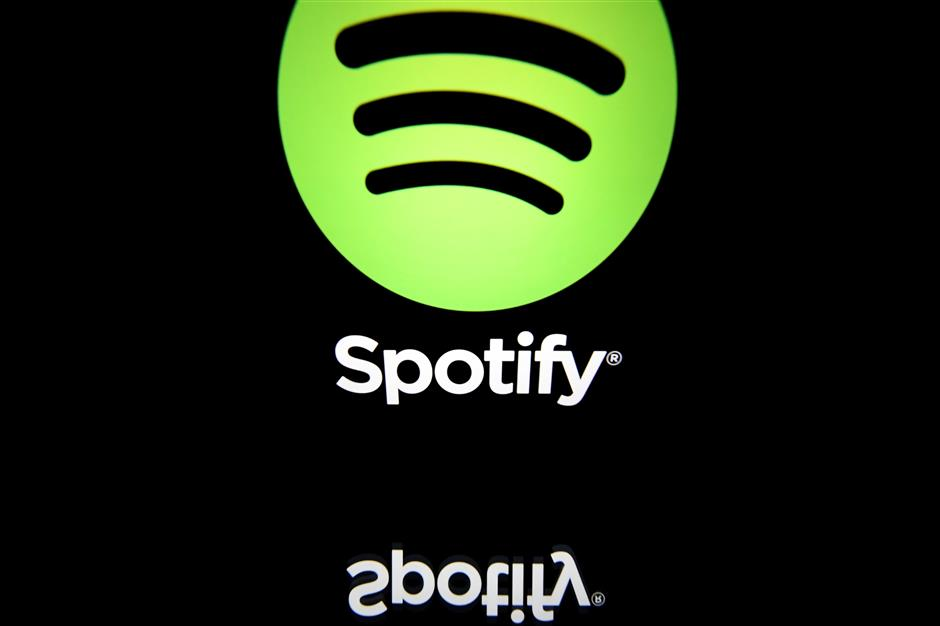 (FILES) In this file photo illustration taken on April 19, 2018 shows the logo of online streaming music service Spotify displayed on a tablet screen in Paris. - Spotify, the world\'s leading music streaming platform, on February 6, 2019 announced an ambitious plan to become a top streamer of podcast content.The Sweden-based company plans to invest $500 million on non-music streaming this year, seeking to dominate its listener base by scooping up American podcasting companies Gimlet Media and Anchor. (Photo by Lionel BONAVENTURE / AFP)