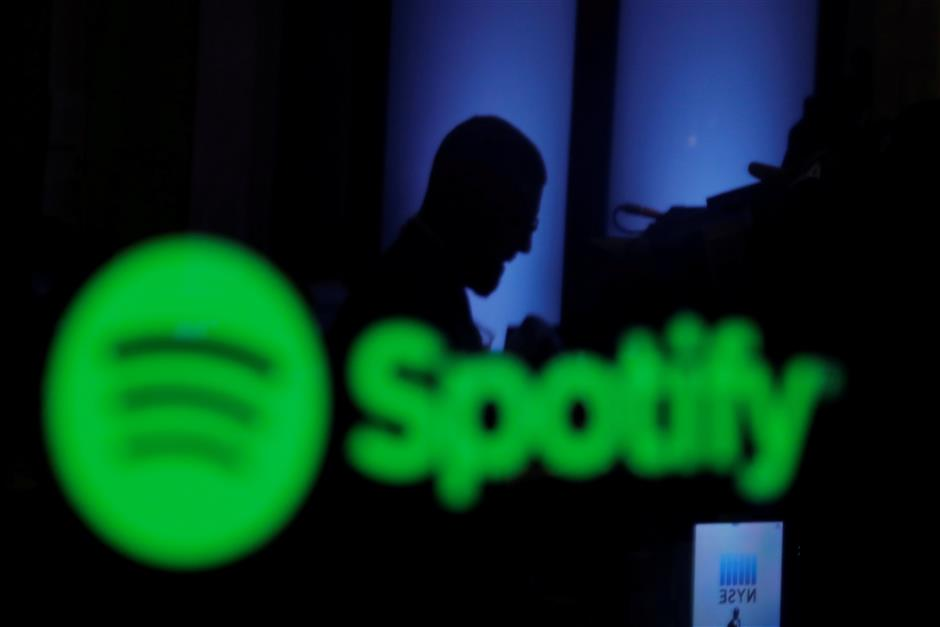 FILE PHOTO: A trader is reflected in a computer screen displaying the Spotify brand before the company begins selling as a direct listing on the floor of the New York Stock Exchange in New York, U.S., April 3, 2018.  REUTERS/Lucas Jackson/File Photo                        GLOBAL BUSINESS WEEK AHEAD