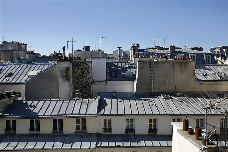 In this Tuesday, Sept. 11, 2018 photo, a view of rooftops in downtown Paris. The spectacular growth of Airbnb in Paris, the top worldwide location for the internet giant is also raising alarms in the French capital. Some Parisians and officials at City Hall blame the site for driving Parisian families out of the city center, leading to school closures and concerns that the French capital is losing its life and charms. (AP Photo/Thibault Camus)