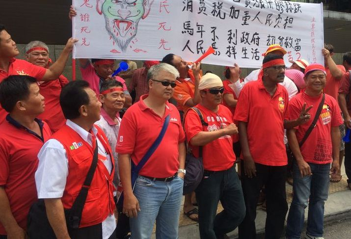 Protesters holding up banners at the Anti-GST rally.
