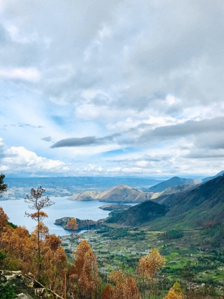 The towering mountains and drifting clouds of Lake Toba.