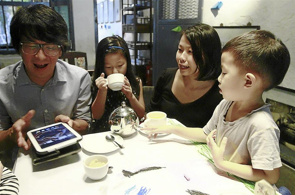 Interior designer Adrian Tan (left) with his wife Ashley Teoh, (second right) recalling the story behind the mural