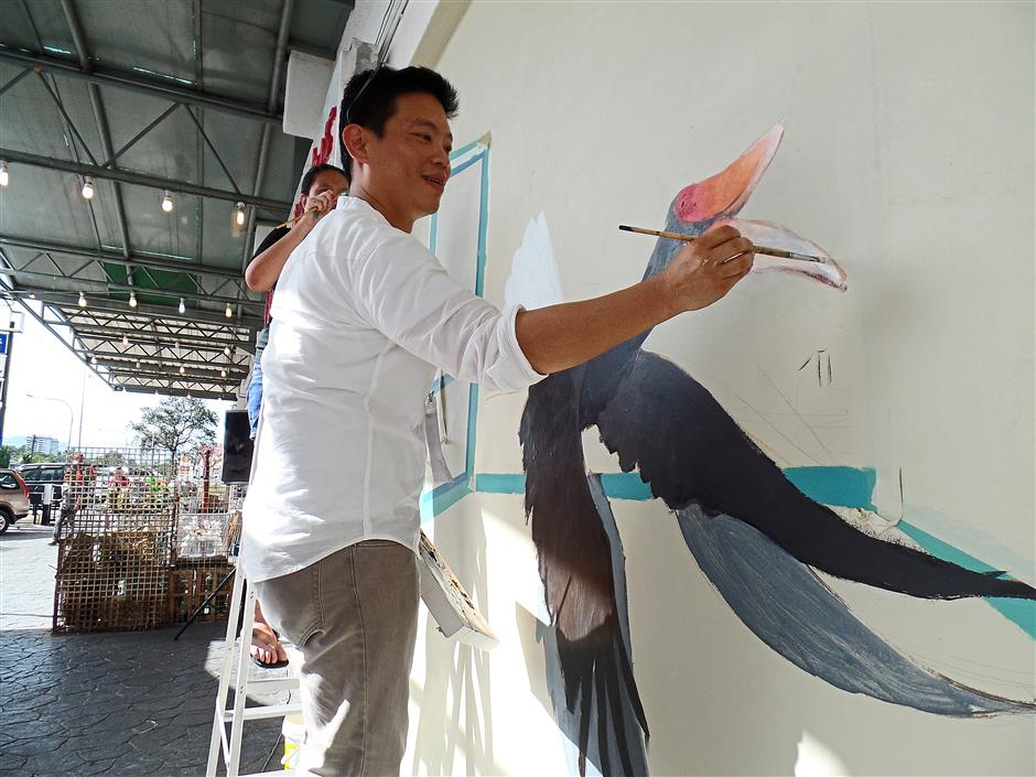 Artistic: Goh painting on the wall of Kenyalang Commercial Park.