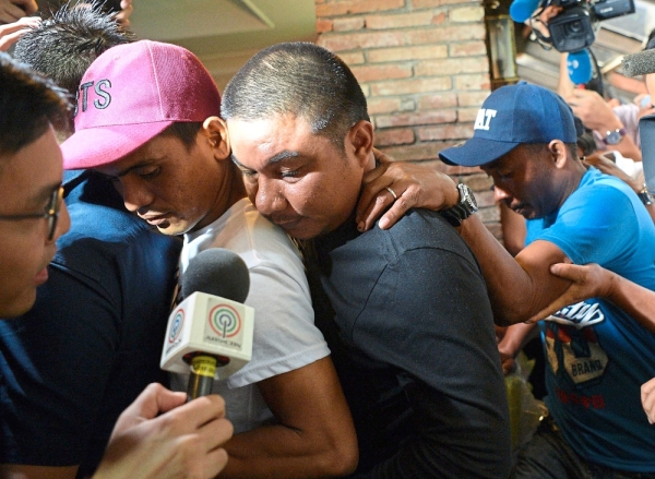 In the media glare: (From left) Filipino crewmembers Jaypee Gordiones, Felix Dela Torre and Richard Blaze being mobbed by journalists after a press conference  in Manila.  u2014 AFP