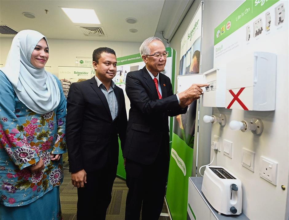 (From left) Iffah, Schneider Electric senior product marketing engineer Mazliazhar Abdul Latif and Chew demonstrating how to push the RCD button during the electrical safety discussion.