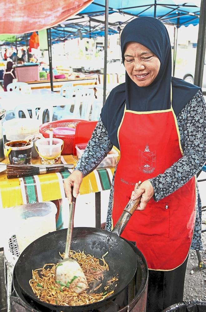 Salmiah preparing mee goreng at the open-air stall.