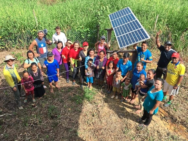 Power for the people: Tambakau (in red cap) and representatives of the association with the local community at Kampung Sonsogon Magandai for the installation of a solar panel.