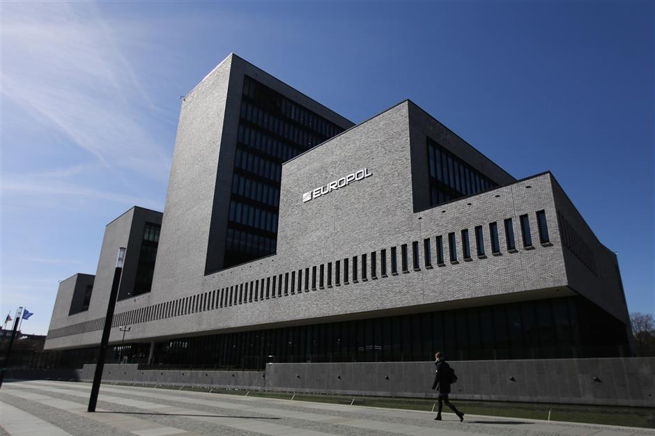 """A pedestrian passes outside the Europol headquarters in The Hague, Netherlands, on Tuesday, March 20, 2018. Europol Executive DirectorRob Wainwrightis leaving the EU intelligence agency he's led for almost a decade to help runDeloitte LLP's cybersecurity practice, as companies wake up to the growing """"systemic"""" threat of cyber crime. Photographer: Yuriko Nakao/Bloomberg"""