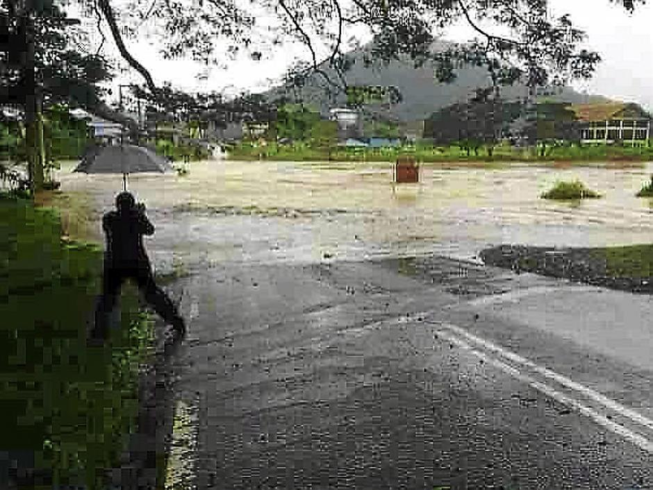 A photographer takes a picture of the swollen Tamparuli river that has completely submerged a low lying bridge.